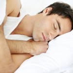 Closeup portrait of a young man sleeping on the bed